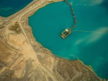 widok z lotu ptaka bagrownica uzupełnia piasek w błękitnym jeziorze zdjęcia stock