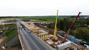 Widok z lotu ptaka bridżowej budowy teren z dwa żurawiami niedaleka jezdnia i pole zbiory wideo