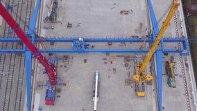 Widok z lotu ptaka czerwoni i żółci budowa żurawie instalował blisko żółtych ładunków zbiorników i kolei w zdjęcie wideo