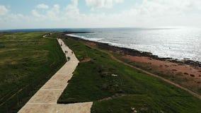 Widok z lotu ptaka denna linia brzegowa z pedestrians chodzi wzdłuż plaży Paphos Cypr deptak Trutnia widok morza i seashore dowci zbiory wideo