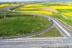 Widok z lotu ptaka drogowy omijanie przez wiejskiego krajobrazu z kwiatem Fotografia Stock