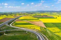 Widok z lotu ptaka drogowy omijanie przez wiejskiego krajobrazu z kwiatem Zdjęcia Stock