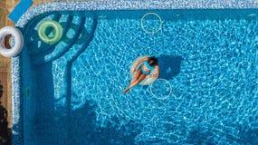 Widok z lotu ptaka dziewczyna w pływackim basenie od above, dzieciaka pływanie na nadmuchiwanym ringowym pączku, zabawa w wodzie  Zdjęcia Stock