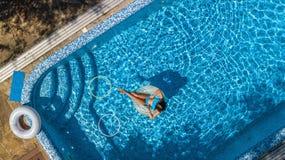 Widok z lotu ptaka dziewczyna w pływackim basenie od above, dzieciaka pływanie na nadmuchiwanym ringowym pączku, zabawa w wodzie  Fotografia Stock