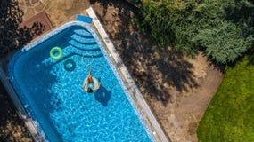 Widok z lotu ptaka dziewczyna w pływackim basenie od above, dzieciaka pływanie na nadmuchiwanym ringowym pączku, zabawa w wodzie  Zdjęcie Royalty Free