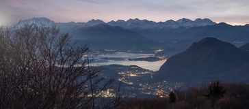 Widok z lotu ptaka Jeziorny Maggiore przy półmrokiem z śniegiem nakrywał Alps, Włochy zdjęcia stock