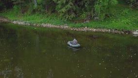 Widok z lotu ptaka mężczyzna w coverall połowie w gumowej łodzi na rzece blisko strony z roślinami, krzakami i drzewami, wewnątrz zdjęcie wideo