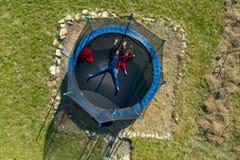 Widok z lotu ptaka matka z jej córką ma zabawę na trampoline trutniem fotografia stock