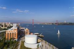 Widok z lotu ptaka miasto Lisbon z żagiel łodziami na Tagus rzece i 25 Kwietnia most na tle Obrazy Stock