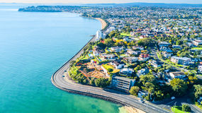 Widok z lotu ptaka na drogowym bieg wzdłuż dennego brzeg z mieszkaniowymi przedmieściami na tle nowy auckland Zelandii Obraz Royalty Free