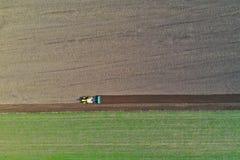 Widok z lotu ptaka na połysku obszarze wiejskim z starym ciągnikiem podczas gdy orzący ziemię na pszenicznym polu przed siać ziar fotografia stock
