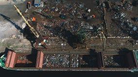 Widok z lotu ptaka na pracującym żurawiu przy złomowym rozsypiskiem ładuje żelazo zdjęcie wideo