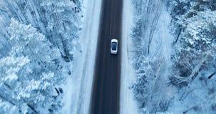 Widok z lotu ptaka na samochodowym jeżdżeniu na zimy wiejskiej drodze w śnieżnym lesie zbiory