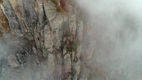 Widok z lotu ptaka na skalistej zbocze góry w chmurach zakrywał małych drzewa z zieleni, koloru żółtego i czerwieni liśćmi, strza zbiory