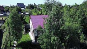 Widok z lotu ptaka na wieś z budynkiem i drewnem. Klip. Widok z góry domów wiejskich zbiory