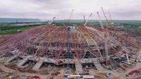 Widok z lotu ptaka na wielkim sporta stadium w budowie, budujący maszynerię umieszcza wokoło zdjęcie wideo