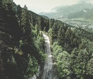 Widok z lotu ptaka nad halną drogą iść przez lasu krajobrazu Fotografia Stock