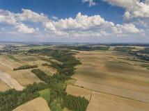 Widok z lotu ptaka niebieskiego nieba i wioski żniwa pola przy latem Zdjęcia Stock