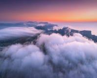 Widok z lotu ptaka niskich chmur, gór, dennego i kolorowego niebo przy zmierzchem, fotografia stock