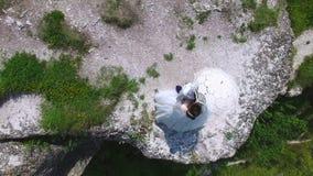 Widok z lotu ptaka para nowożeńcy stoi na falezy całowaniu zbiory wideo