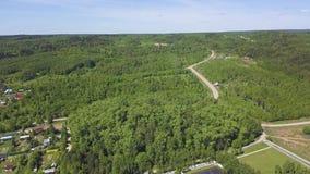 Widok z lotu ptaka podmiejski teren z wiele zielonymi drzewami i drogą pod lata niebem klamerka Miasteczko wśród zalesionego zbiory