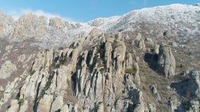 Widok z lotu ptaka rockowa formacja przeciw niebu zakrywającym zamarzniętymi krzakami błękitnemu jasnemu wierzchołkowi góra i str zdjęcie wideo