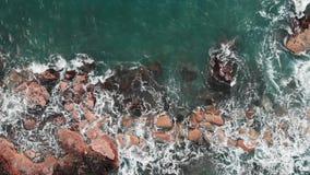 Widok z lotu ptaka silne fale uderza skały i bryzgać Trutnia widok jasna błękitna ocean woda z biel pianą zbiory wideo