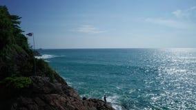 Widok z lotu ptaka skalistej wyspy wybrzeże z Tajlandzką flagą i rybakiem nad tłem morza i nieba zbiory wideo