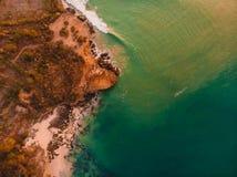 Widok z lotu ptaka skalisty brzeg z oceanu zmierzchem i falami zdjęcie stock