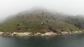 Widok z lotu ptaka skalisty brzegowy Halny turkusowy jezioro wśród wzgórzy w chmurnej pogodzie i mgle Krajobrazy północ zdjęcie wideo