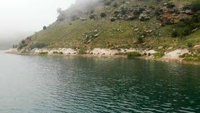 Widok z lotu ptaka skalisty brzegowy Halny turkusowy jezioro wśród wzgórzy w chmurnej pogodzie i mgle Krajobrazy północ zbiory wideo