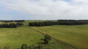 Widok z lotu ptaka skrzyżowania SUV samochodowy jeżdżenie wzdłuż żwir drogi przez zielonego łąka krajobrazu zbiory