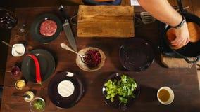 Widok z lotu ptaka szef kuchni w błękitnej fartuch pozycji blisko stołu z składnikami dla robić hamburgery i smażyć babeczki na a zbiory wideo