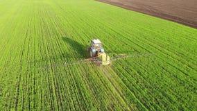 Widok z lotu ptaka uprawia? ziemi? ci?gnikowego opryskiwanie na polu z natryskownic?, herbicydami i pestycydami przy zmierzchem,  zbiory
