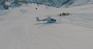 Widok z lotu ptaka, wokoło Heliskiing helikopteru i grupy narciarki, snowboarders w zim górach zdjęcie wideo