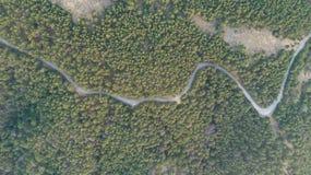 Widok z lotu ptaka wsi drogowy omijanie przez zielony forrest halny przy zmierzchem i zdjęcia stock