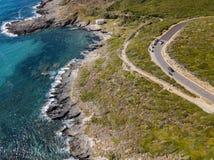 Widok z lotu ptaka wybrzeże Corsica, wijące drogi i zatoczki, Motocykliści parkujący na krawędzi drogi Francja zdjęcie stock
