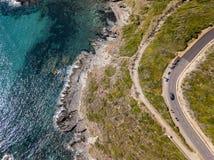 Widok z lotu ptaka wybrzeże Corsica, wijące drogi i zatoczki, Motocykliści parkujący na krawędzi drogi Francja zdjęcia royalty free