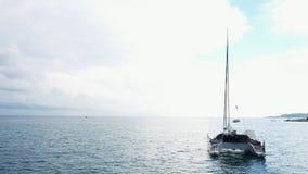 Widok z lotu ptaka zakotwiczaj?ca catamaran jachtu pozycja i ludzie konserwujemy sunbathing na nim jeste?my pok?adem zbiory wideo