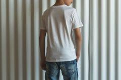 widok z powrotem Młoda modniś chłopiec ubierająca w białej koszulce jest stojakami salowymi przeciw biel ścianie Egzamin próbny U Obrazy Stock