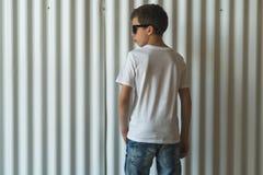 widok z powrotem Młoda modniś chłopiec ubierająca w białej koszulce jest stojakami salowymi przeciw biel ścianie Egzamin próbny U Zdjęcia Stock