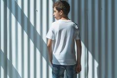 widok z powrotem Młoda modniś chłopiec ubierająca w białej koszulce jest stojakami salowymi przeciw biel ścianie Egzamin próbny U Obrazy Royalty Free