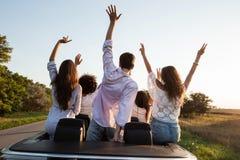 widok z powrotem Młodzi faceci są siedzący ręki w górę czarnego kabrioletu na wiejskiej drodze na słonecznym dniu wewnątrz i trzy obraz stock