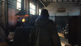 Widok z tyłu mężczyzny w ochronnych coveralls i czarnej nakrętce iść na starej steelmaking roślinie blisko roztapiającego pa zbiory