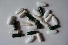 Widok zielone kapsuły multivitamins, biali caplets wapnie i białe kapsuły magnez, z góry zdjęcie royalty free