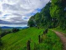 Widok zielonej trawy pole wokoło gór z sposobu cros Obrazy Stock