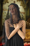 Widow in black. Very cute widow in black dress and veil on face inside a church Royalty Free Stock Image