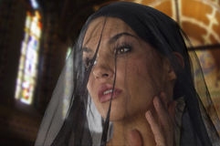 Widow in church. Cute woman like widow with a black transparent veil on her face in church Stock Image