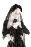 Widow doll girl. Widow in a black dress with white eyes looking like a doll isolated in white Royalty Free Stock Image