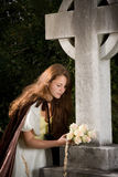 Widow with flowers. Young victorian widow putting flowers on a grave Royalty Free Stock Image